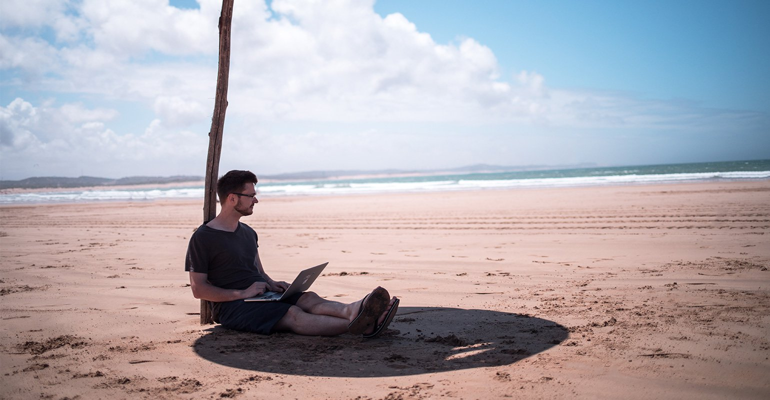 A man sitting on the beach under umbrella thinking: Remote work: opportunity or threat?