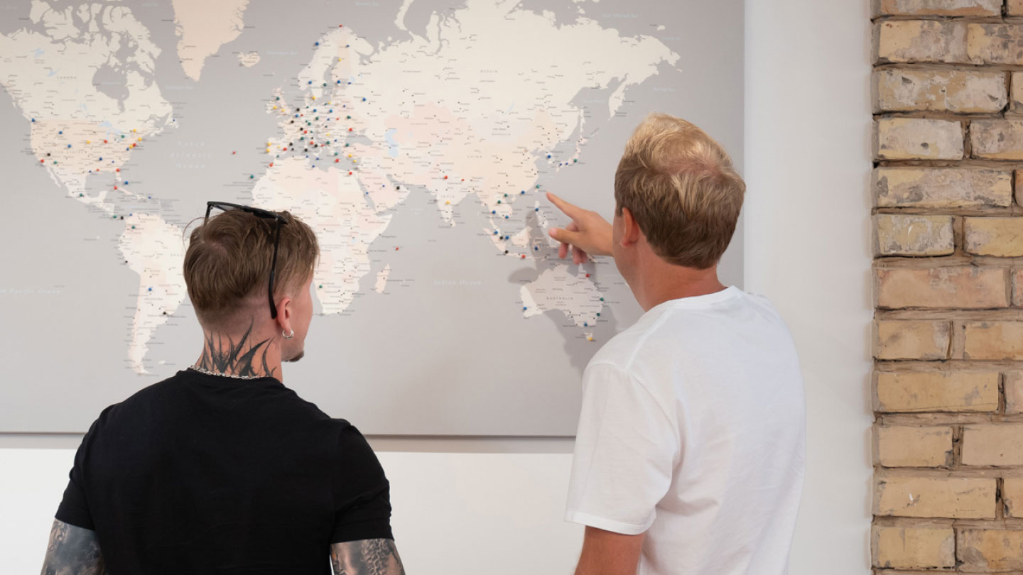 Two employees of The Remote Company are standing in front of the world map, looking for their next destination for remote work..